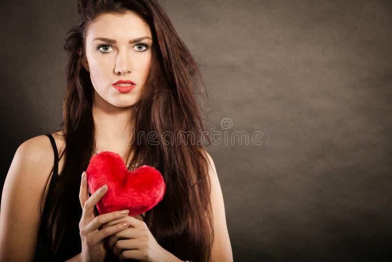 Красивая женщина держит красное сердце на черноте стоковое изображение rf