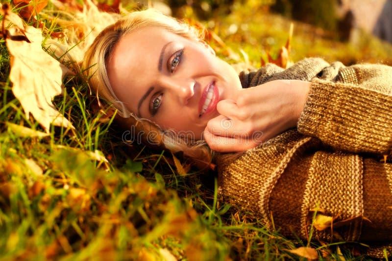Красивая женщина лежа вниз на листьях осени стоковые фотографии rf