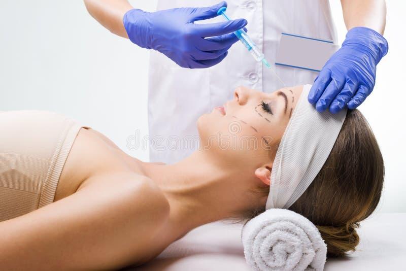 Красивая женщина лежа в клинике, пластический хирург в руках иглы стоковое фото