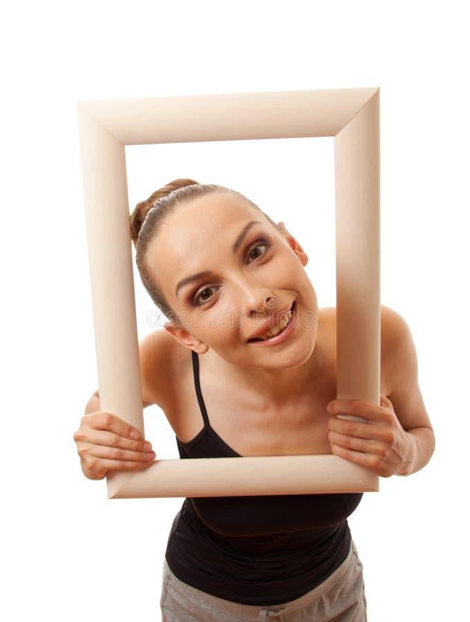 Красивая женщина держа рамку и усмехаться стоковое изображение