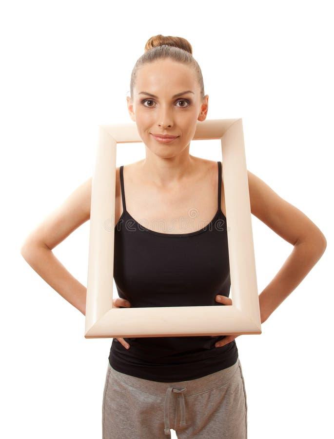 Красивая женщина держа рамку и усмехаться стоковая фотография rf