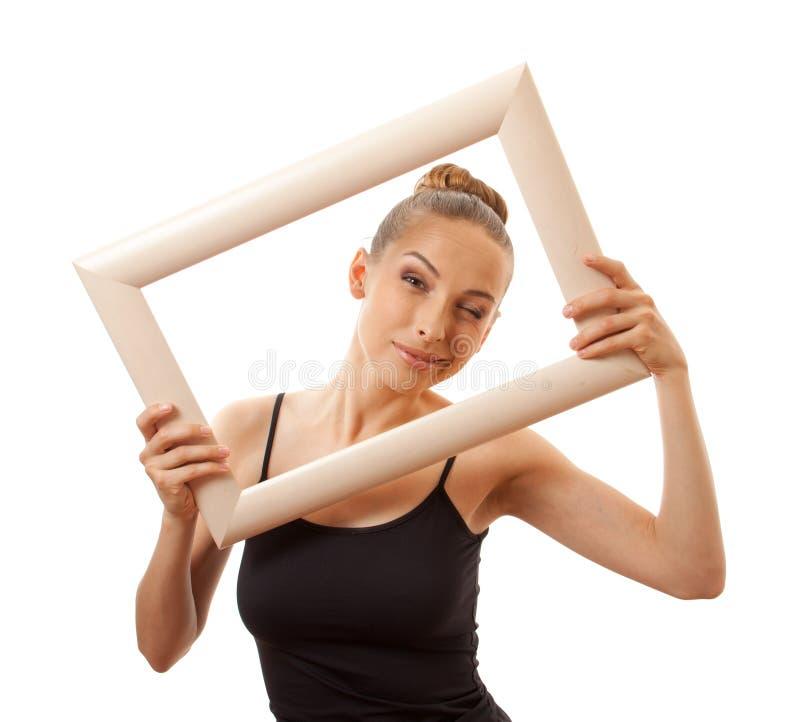 Красивая женщина держа рамку и усмехаться стоковые изображения