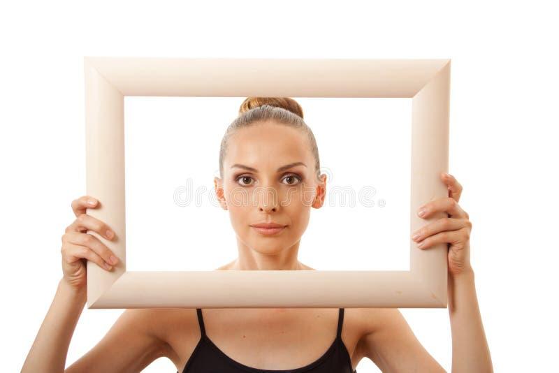 Красивая женщина держа рамку и усмехаться стоковые фото