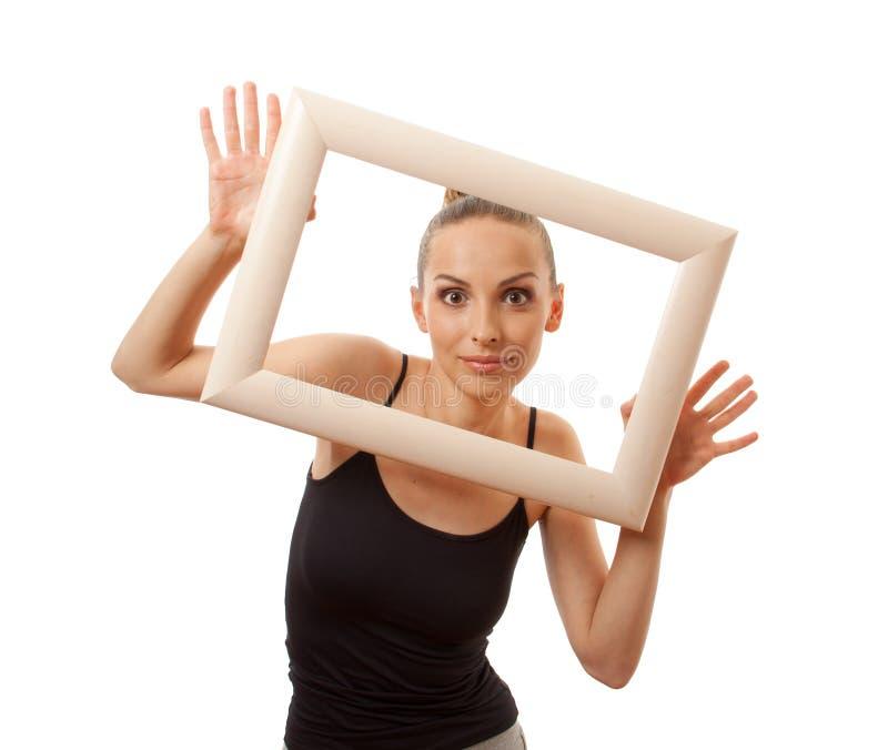 Красивая женщина держа рамку и усмехаться стоковое изображение rf