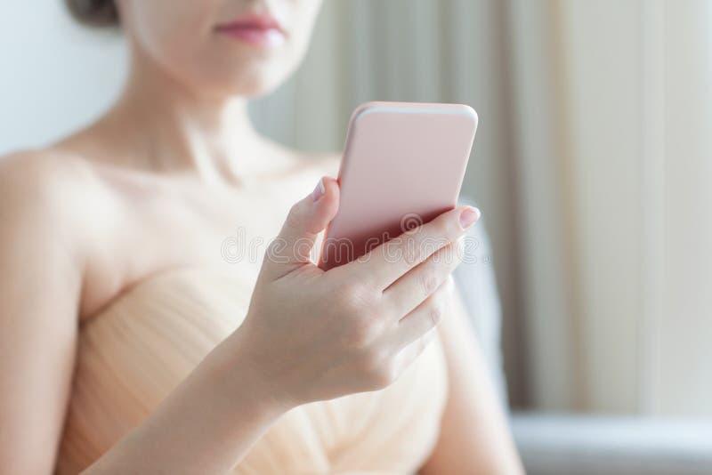 Красивая женщина держа розовый телефон стоковые изображения rf