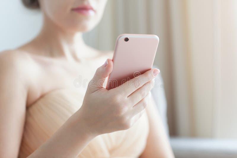 Красивая женщина держа розовый телефон стоковая фотография rf