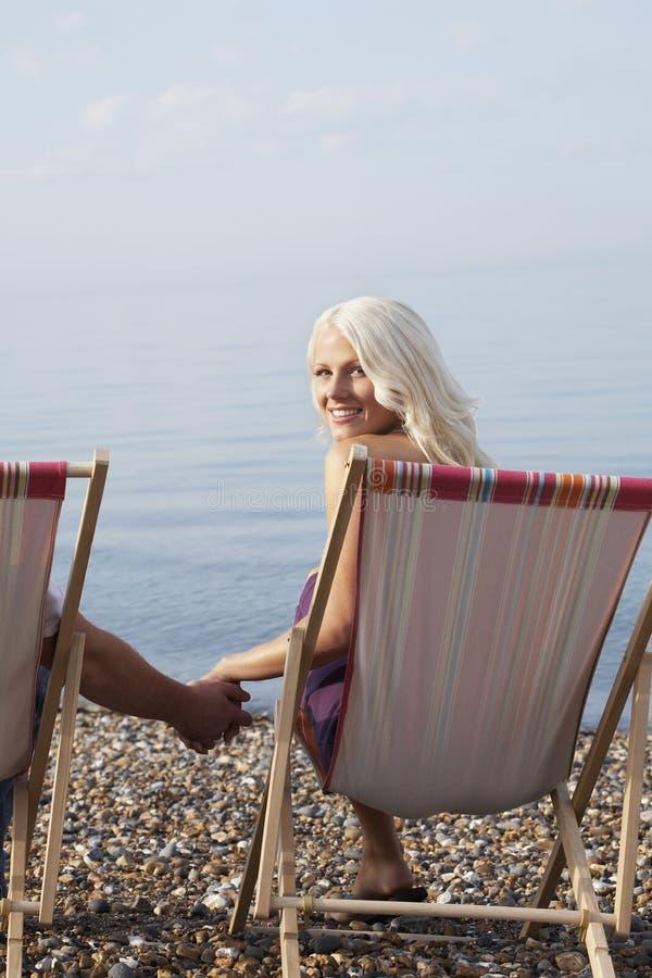 Красивая женщина держа руку человека пока сидящ на Deckchair стоковое изображение rf
