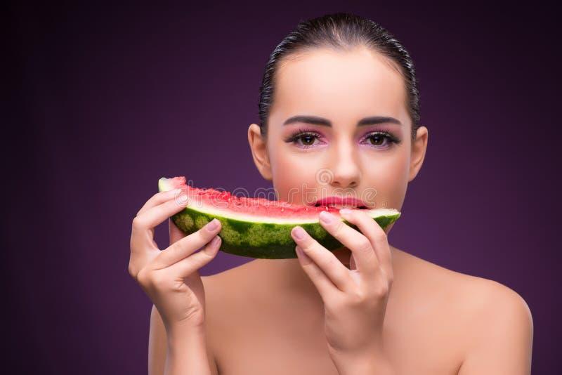 Красивая женщина есть вкусный арбуз стоковая фотография rf