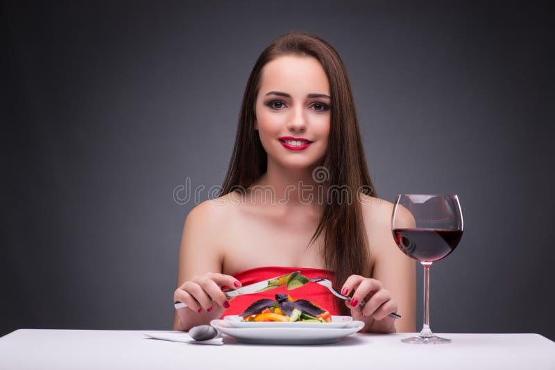 Красивая женщина есть самостоятельно с вином стоковые фотографии rf