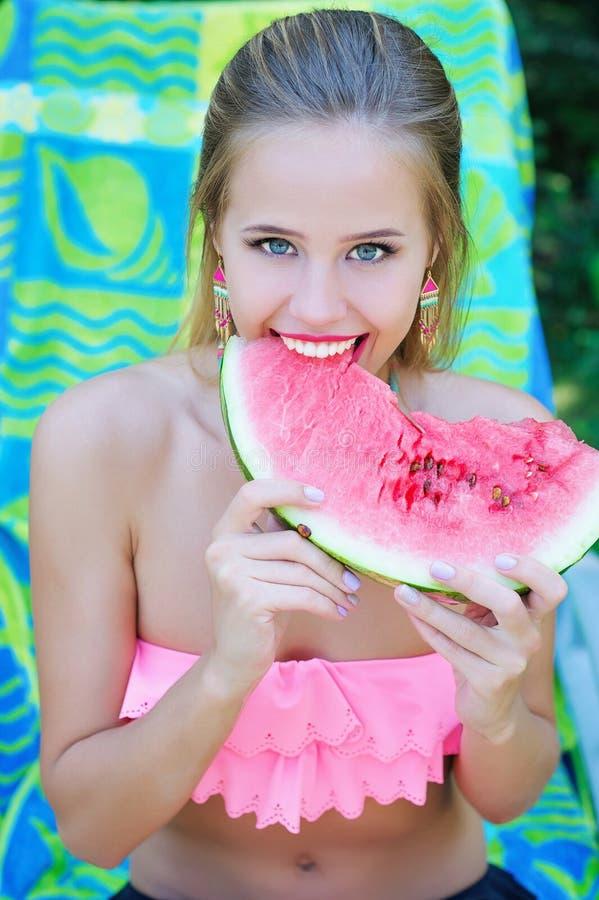 Красивая женщина есть сладостный арбуз стоковые фото