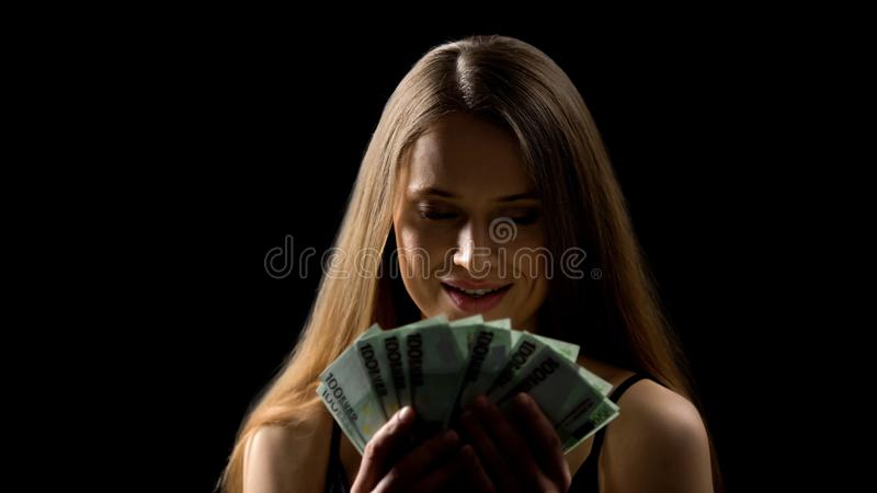 Красивая женщина жадно смотря деньги, наслаждаясь доходом, джэкпот лотереи стоковое изображение rf