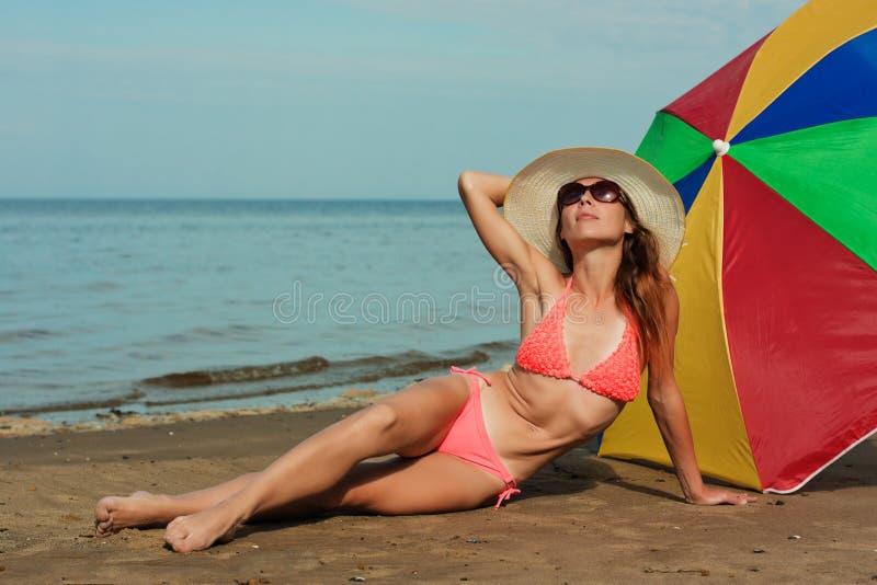 Красивая женщина загорая на пляже. стоковая фотография rf
