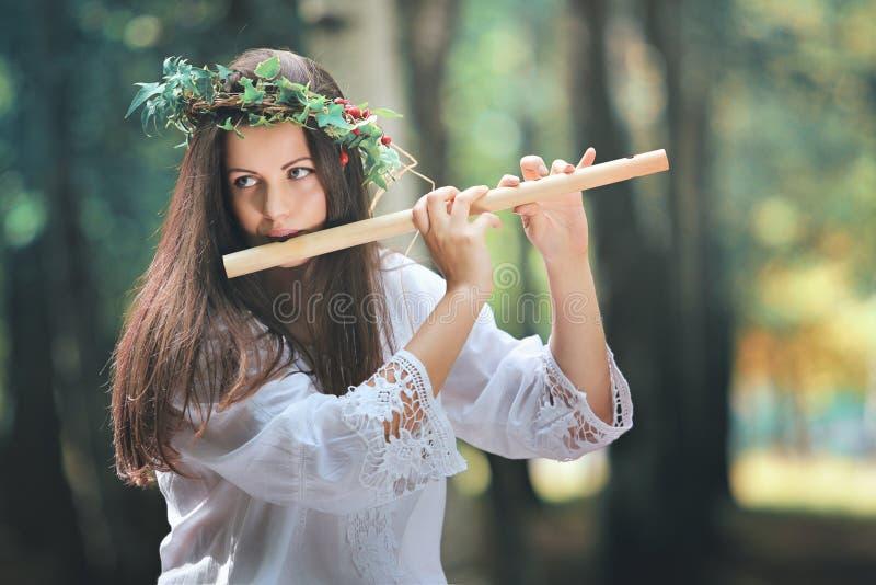 Красивая женщина играя каннелюру в лесе стоковые фотографии rf