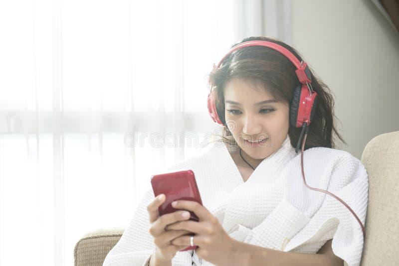 Красивая женщина играя телефон в спальне счастливо в утре стоковое изображение rf