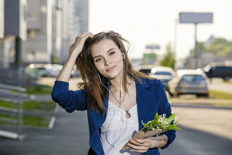 Красивая женщина идет через улицы слушая к музыке на наушниках с букетом стоковые фото