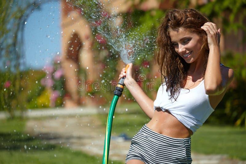 Красивая женщина имея потеху в саде лета с садом ho стоковые фотографии rf