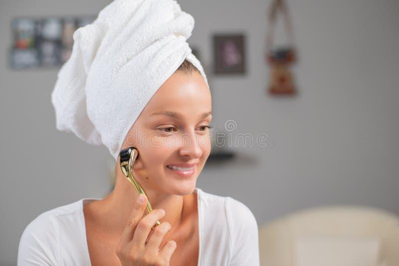 Красивая женщина использует анти-дерма роллер. Женщина делает иглы на Ð стоковая фотография