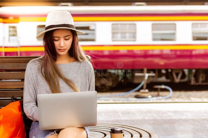 Красивая женщина использует ноутбук на вокзале перед очаровывая красивым азиатским перемещением женщины к назначению Она блоггер  стоковые фото