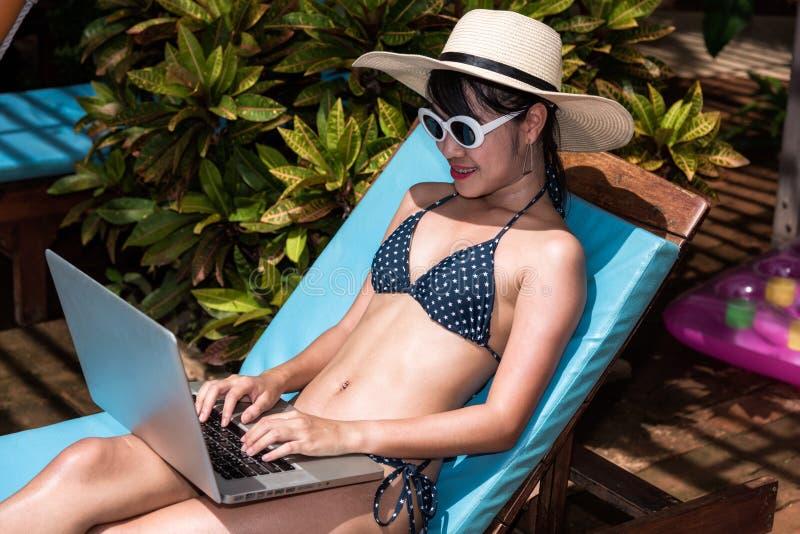 Красивая женщина используя портативный компьютер наслаждаясь ослабляющ сидеть стоковое фото rf