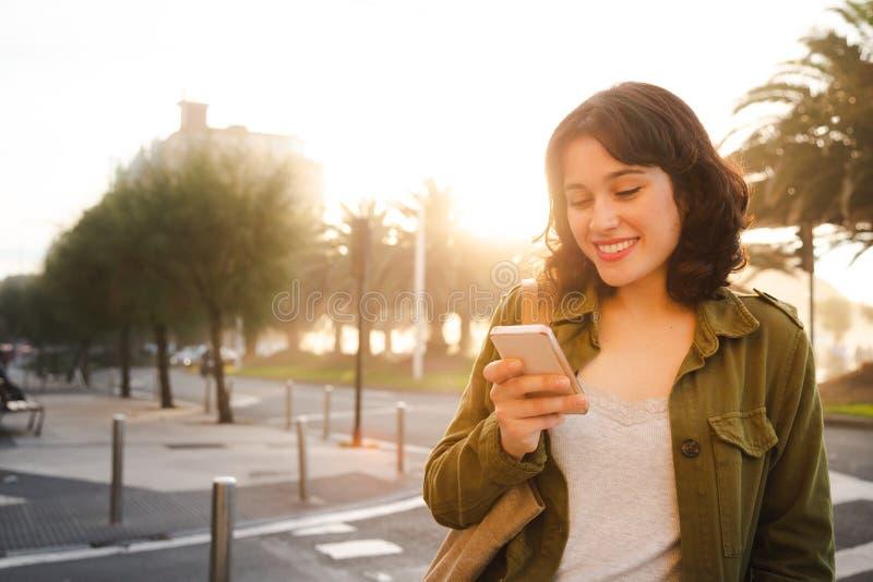 Красивая женщина используя умный телефон в городе стоковая фотография rf