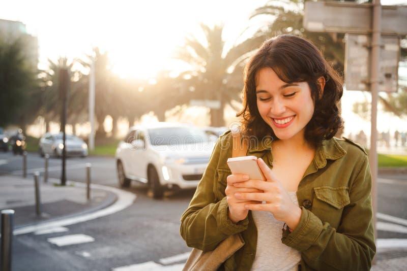 Красивая женщина используя умный телефон в городе стоковое изображение