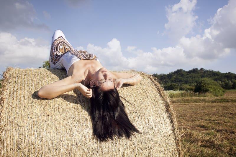 Красивая женщина кладя на сено стоковые изображения rf