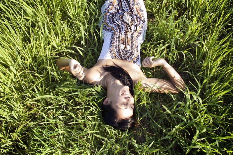 Красивая женщина кладя на траву стоковые фотографии rf