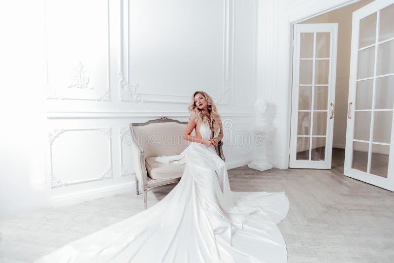 Красивая женщина 30-35 лет в макияже сцены и длинное белое вечернее свадебное платье стоковые изображения