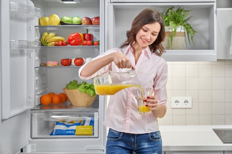 Красивая женщина лить свежий апельсиновый сок в стекле стоковые изображения