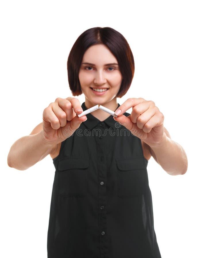 Красивая женщина ломая сигарету изолированную на белой предпосылке Молодость против курить Риск концепции рака стоковая фотография rf