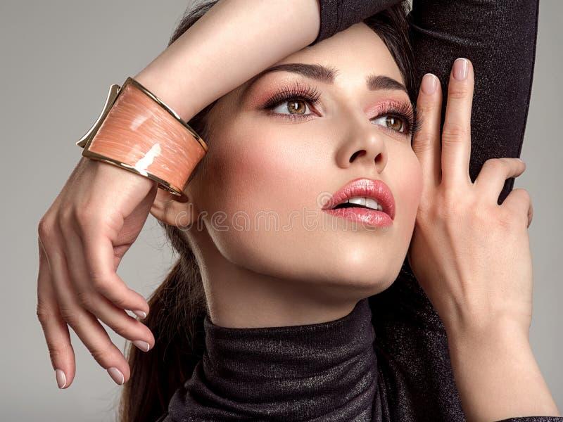 Красивая женщина моды с живя губной помадой коралла Привлекательная белая девушка носит роскошные ювелирные изделия стоковая фотография