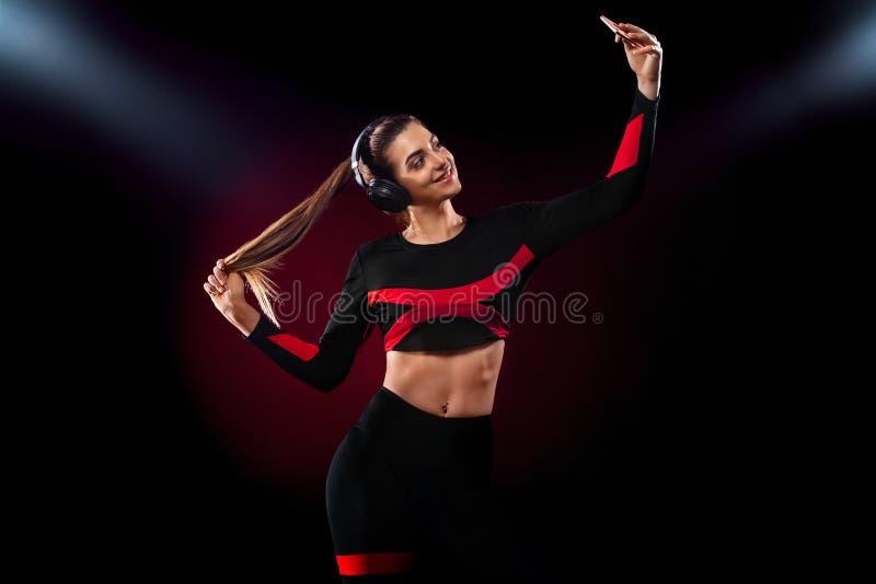 Красивая женщина молодых и пригонке в музыке sportswear и наушников слушая и принимать selfie E стоковые фотографии rf