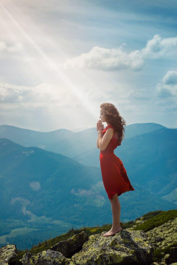 Красивая женщина моля в ландшафте горы стоковые фотографии rf