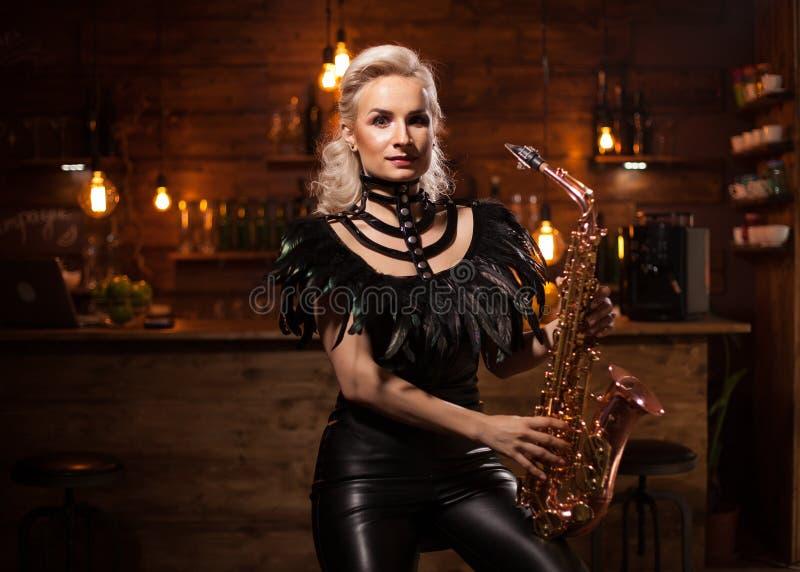 Красивая женщина музыканта в джазовой музыке петь паба на ее саксофоне стоковые фотографии rf