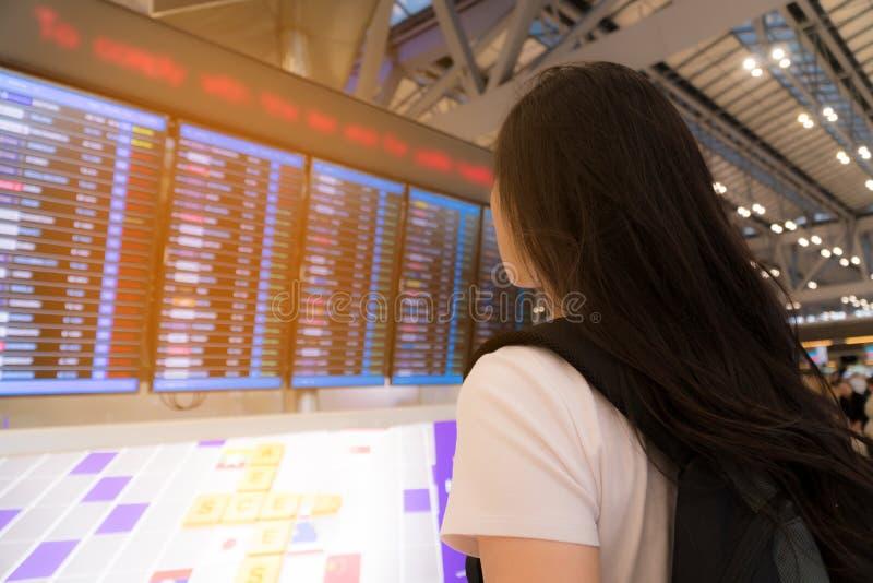 Красивая женщина наблюдая расписание полетов ее отклонения на авиапорте стоковая фотография rf