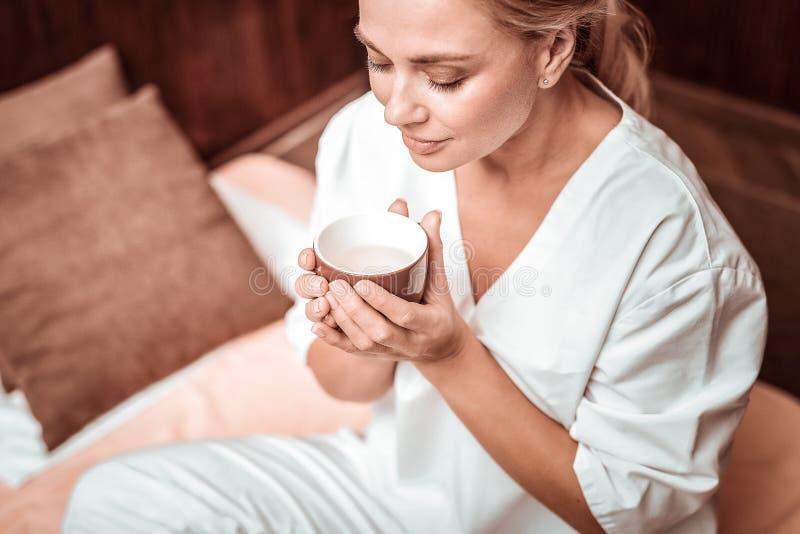 Красивая женщина наслаждаясь вкусом ее чая стоковые фото