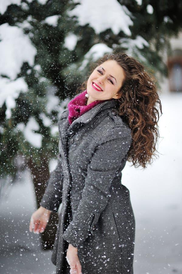 Красивая женщина наслаждается снегом зимы стоковое изображение