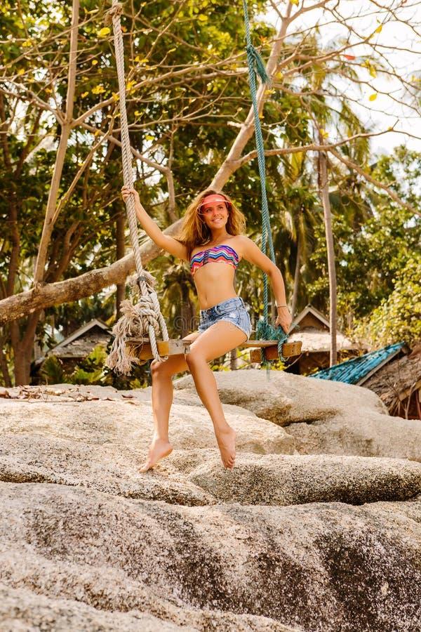 Красивая женщина на качании в тропиках стоковые изображения rf