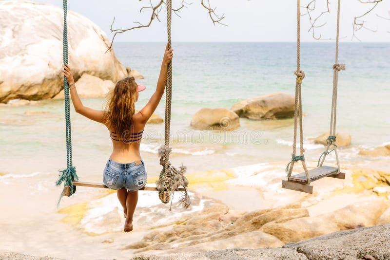 Красивая женщина на качании в тропиках стоковая фотография rf