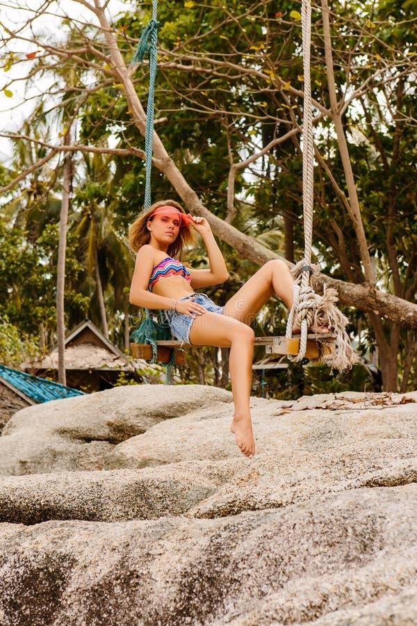 Красивая женщина на качании в тропиках стоковое фото rf
