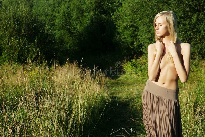 Красивая женщина на поле с одеждами  стоковое изображение rf