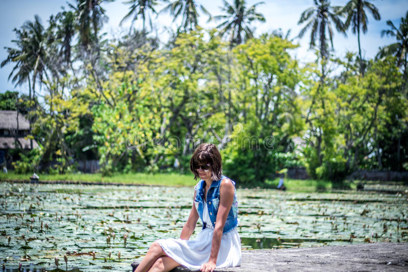 Красивая женщина на поле цветка лотоса, тропический остров Бали, Индонезия стоковая фотография