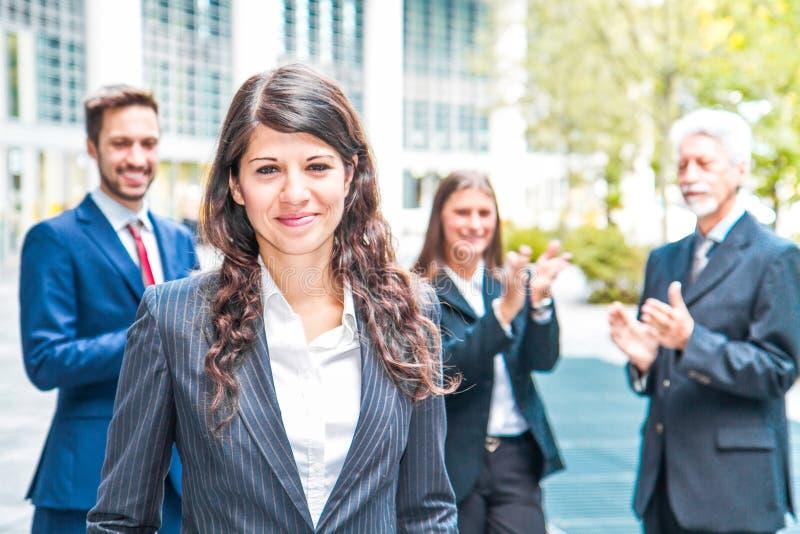 Красивая женщина на предпосылке бизнесменов стоковое изображение