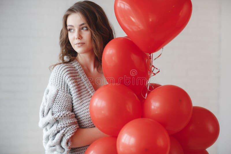 Красивая женщина на серой предпосылке с пуком красных воздушных шаров в форме сердца стоковые изображения rf
