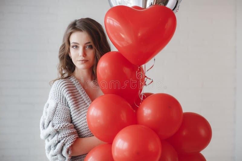 Красивая женщина на серой предпосылке с пуком красных воздушных шаров в форме сердца стоковое фото