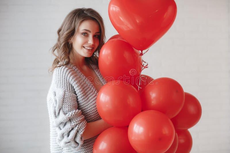 Красивая женщина на серой предпосылке с пуком красных воздушных шаров в форме сердца стоковое фото rf