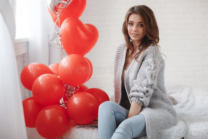 Красивая женщина на серой предпосылке с пуком красных воздушных шаров в форме сердца стоковые фотографии rf