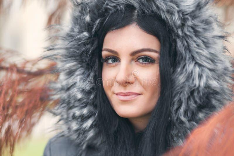 Красивая женщина нося пальто зимы клобука меха стоковое фото rf