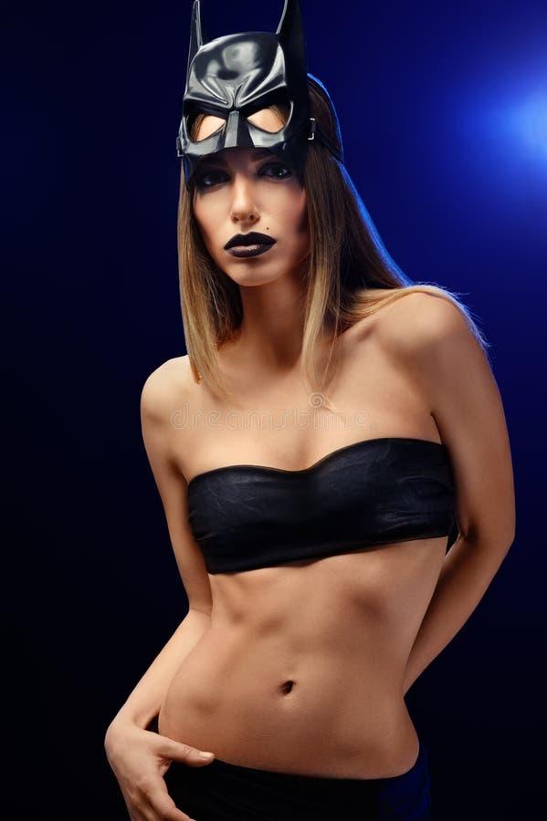 Красивая женщина нося профессиональную маску состава и бэтмэн стоковое изображение rf