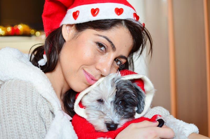 Красивая женщина обнимая ее собаку с красной шляпой рождества стоковое изображение rf
